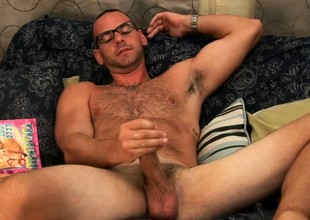 Hot bear in glasses plays with his cock while leafing skim through a gay porn mag