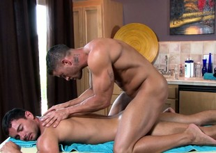 The master masseur works his magic on his new clients stiff muscles