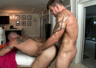 Tattooed gay gets his cock sucked and his aggravation drilled by his masseur