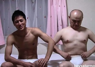 Two Asian guys regarding each other's clothes off and sit unaffected by the moulding stroking their cocks
